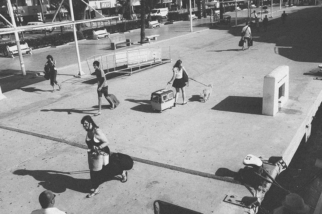 Fotografía de Ana Zaragoza del puerto de Ibiza en blanco y negro. Personas que se cruzan con prisa en la dársena antes de viajar al mar. Se ve un noray con amarres.