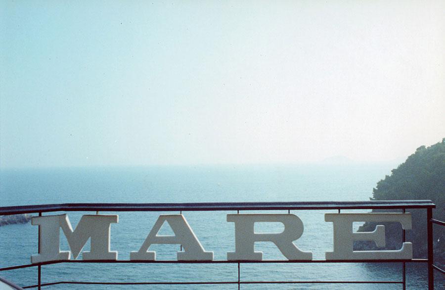 Fotografía de un paisaje de mar del fotógrafo italiano Luigi Ghirri. La toma está hecha desde un mirador en el que la barandilla tiene unas letras que componen la palabra MARE.