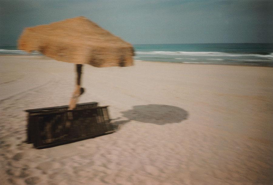 Fotografía de Vari Caramés que muestra una playa con una sombrilla de paja y dos tumbonas de madera recogidas.